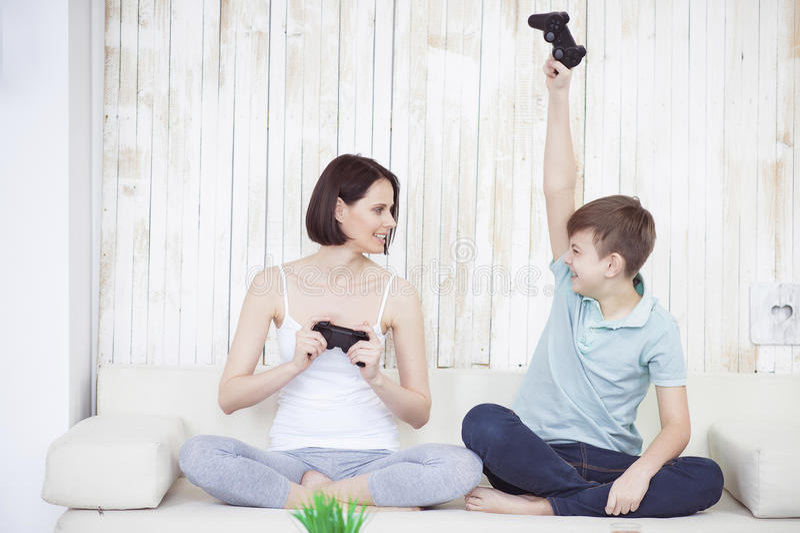 Sira de mãe e seu filho adulto que joga no console fotos de stock