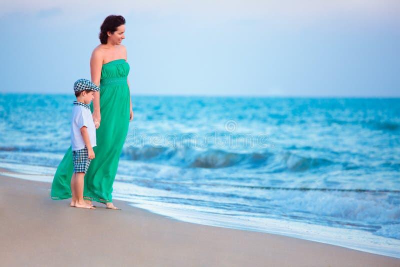 Sira de mãe e seu filho pequeno que aprecia a praia foto de stock royalty free