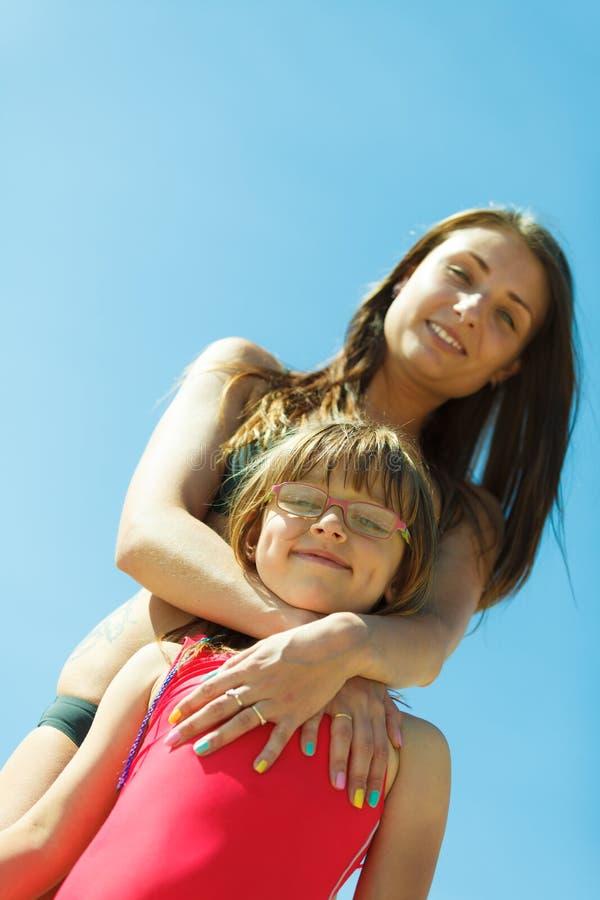 Sira de mãe e sua filha da criança que joga na praia foto de stock