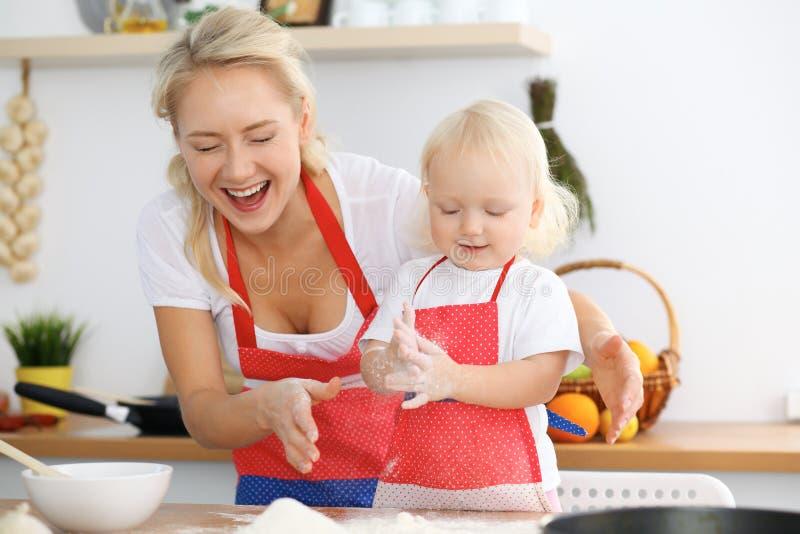 Sira de mãe e sua filha pequena que cozinha a torta ou as cookies do feriado para o dia do ` s da mãe Conceito da família feliz n foto de stock royalty free