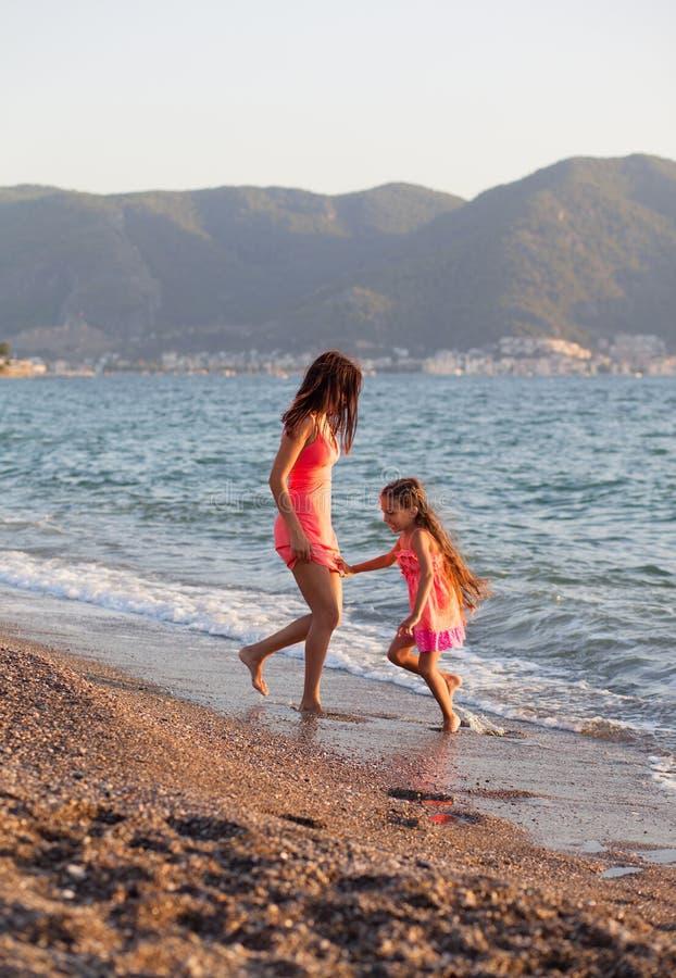 Sira de mãe e sua filha pequena que joga e que corre na praia foto de stock