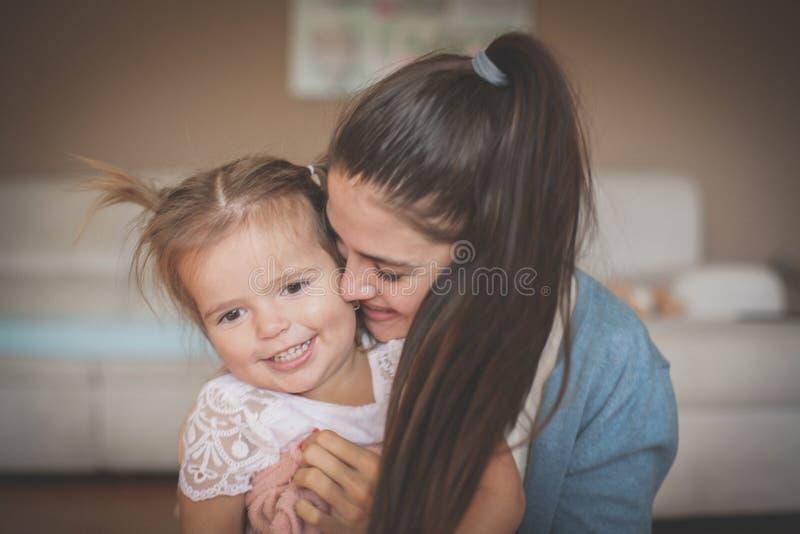 Sira de mãe e sua menina em abraçar a apreciação em casa fotografia de stock