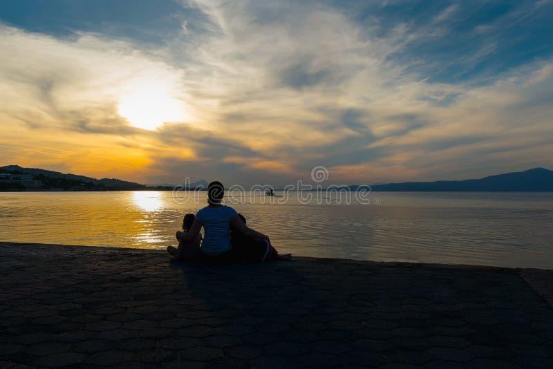 Sira de mãe e suas filhas que olham o por do sol e a silhueta de um barco de pesca Um momento loving da família contra um céu dra imagens de stock royalty free