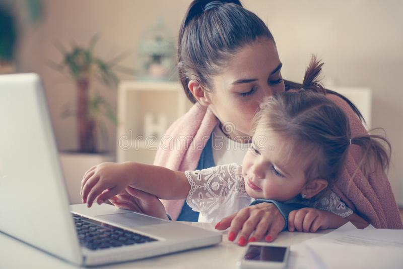 Sira de mãe em casa a beijar sua filha e a usar o toget do portátil fotos de stock