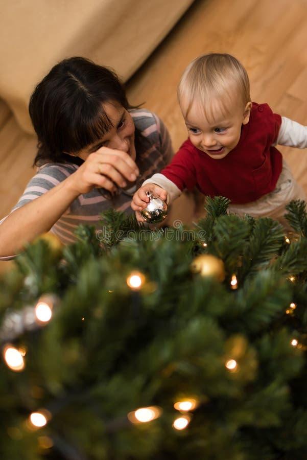Sira de mãe a ensinar seu filho decorar a árvore do xmas fotos de stock