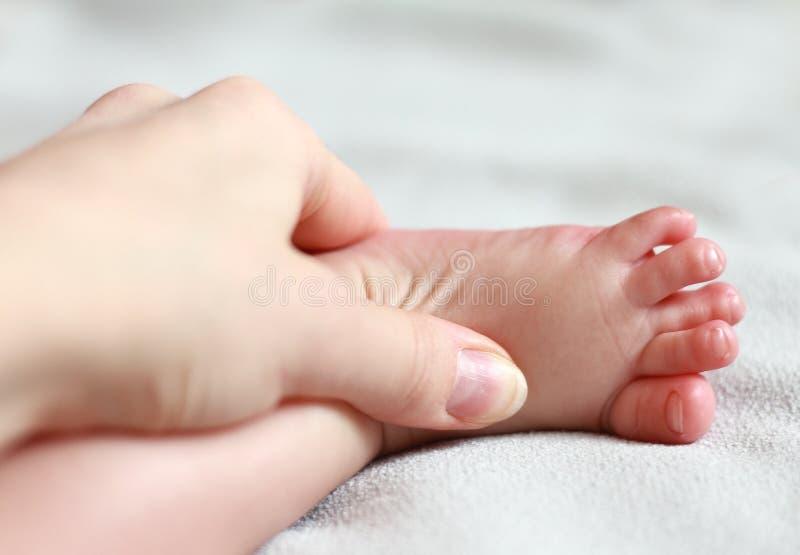 Sira de mãe a fazer massagens o bebê do nascimento novo imagem de stock