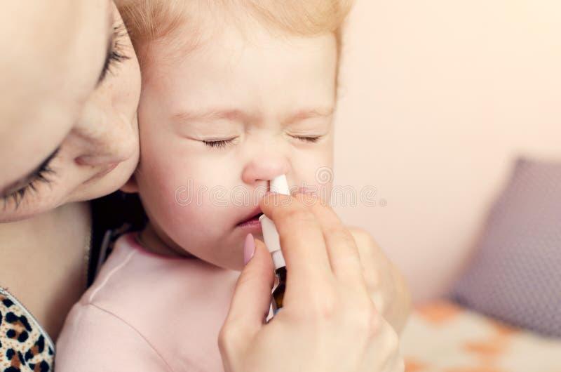 Sira de mãe a gotas dos gotejamentos no nariz de uma criança pequena fotos de stock royalty free