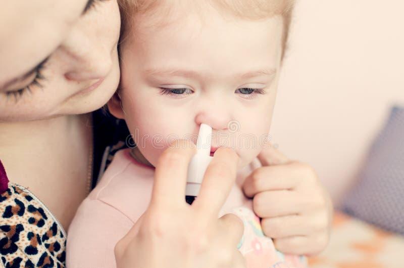 Sira de mãe a gotas dos gotejamentos no nariz de uma criança pequena imagens de stock royalty free