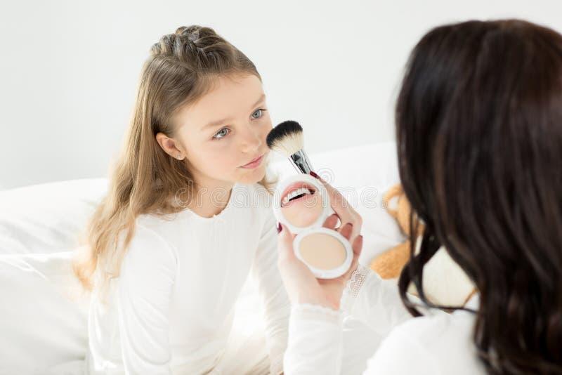 Sira de mãe a guardar o espelho cosmético e escove-o ao aplicar a composição à filha pequena imagem de stock