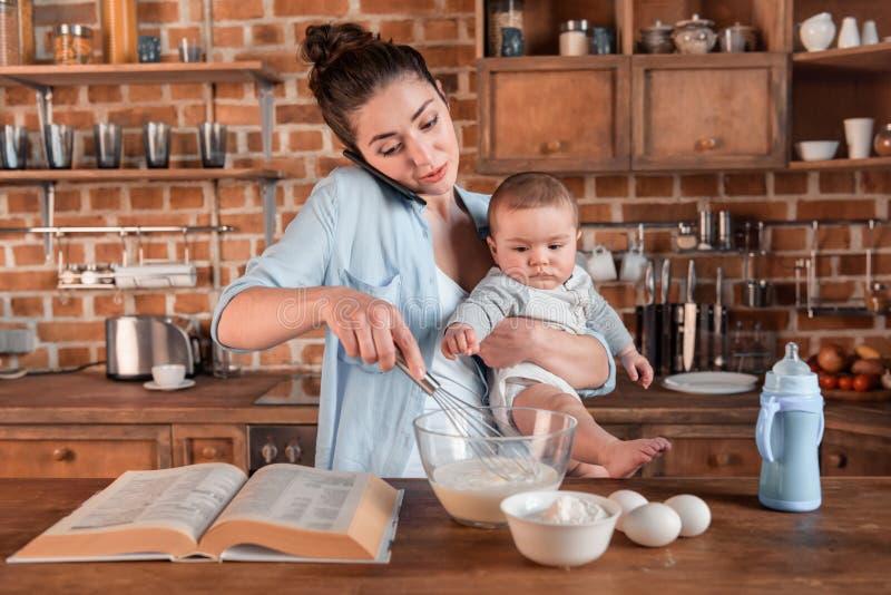 Sira de mãe a guardar seu filho, à fala no smartphone e a misturar uma massa na cozinha conceito da vida familiar e da multitaref imagens de stock
