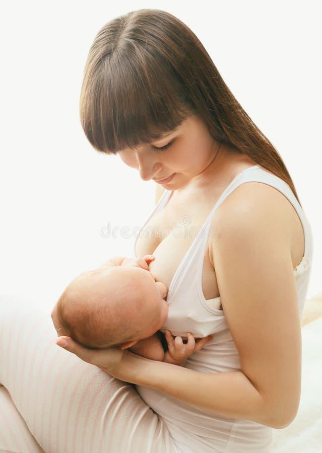 Sira de mãe a guardar sobre entrega o bebê e o peito de alimentação em casa imagens de stock royalty free