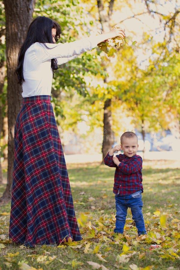 Sira de mãe a jogos com seu filho no parque no outono fotografia de stock