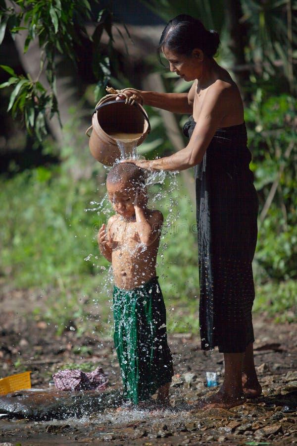Sira de mãe a lavar sua criança derramando o fora de uma cubeta com água em uma rua da vila imagem de stock