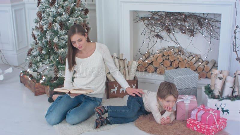 Sira de mãe a ler um livro para seu filho pequeno que encontra-se perto da árvore de Natal fotos de stock royalty free