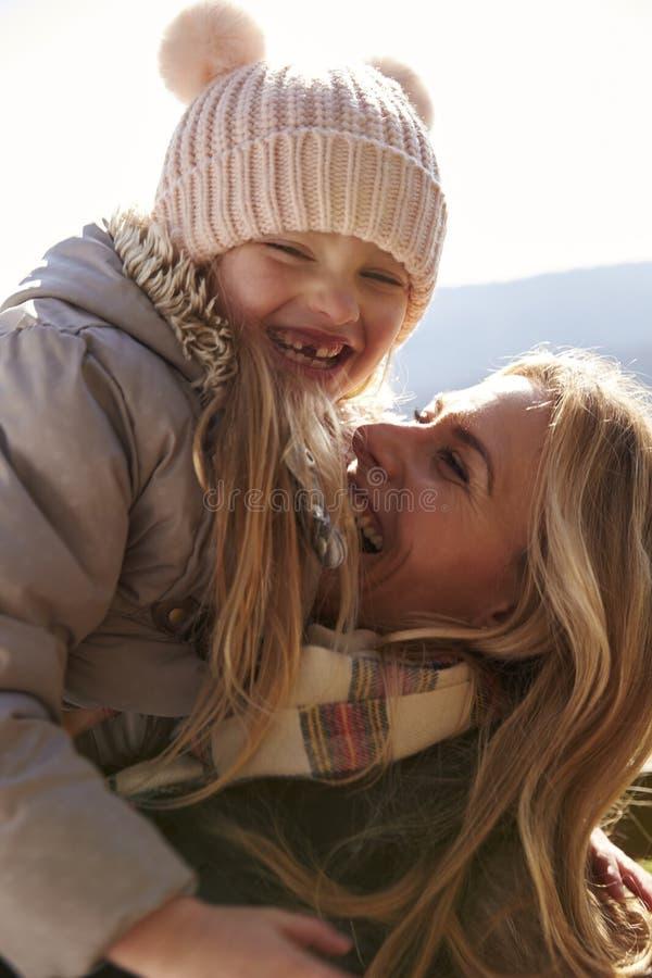 Sira de mãe a levantar sua filha no ar fora, vertical fotografia de stock royalty free