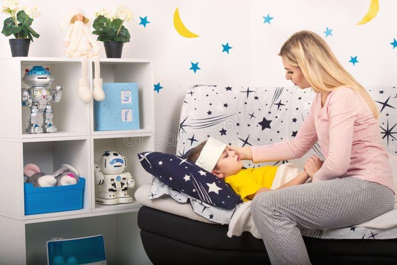 Sira de mãe a medidas a temperatura com sua mão a sua criança Uma criança com a febre que coloca na cama imagens de stock royalty free