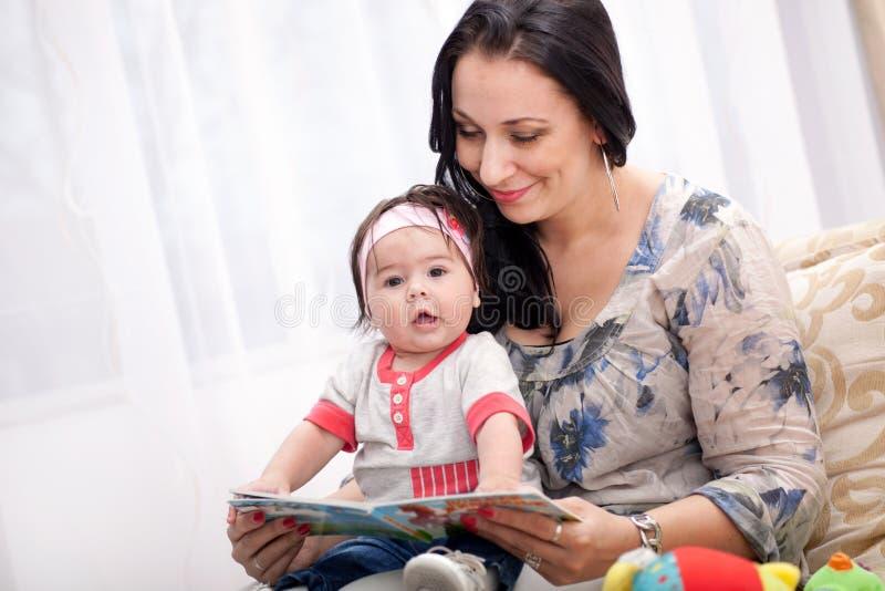 Sira de mãe a mostrar imagens em um livro a sua filha pequena bonito em h fotos de stock