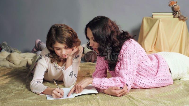 Sira de mãe a mostrar o erro da filha nos trabalhos de casa, corrigindo o exercício, a educação home foto de stock