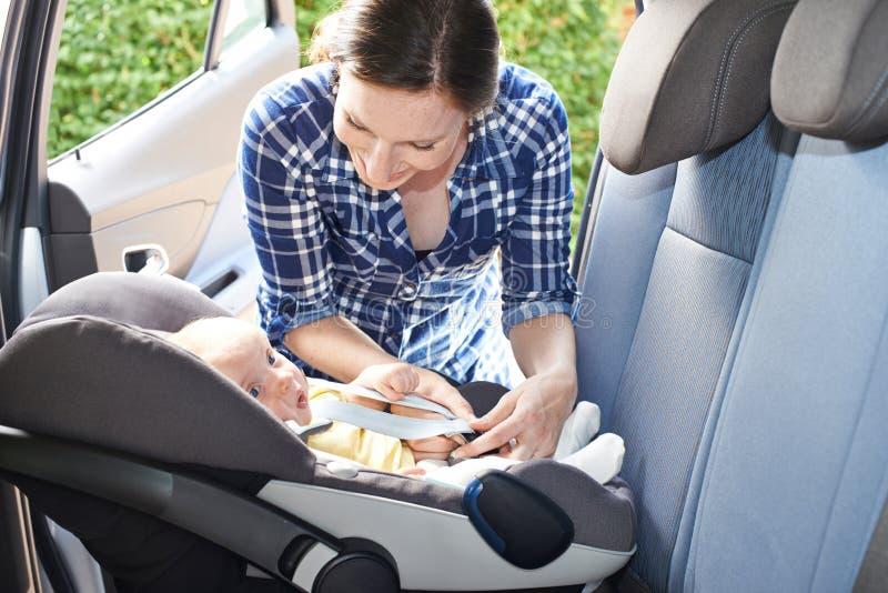 Sira de mãe a pôr o bebê no banco de carro para a viagem imagem de stock