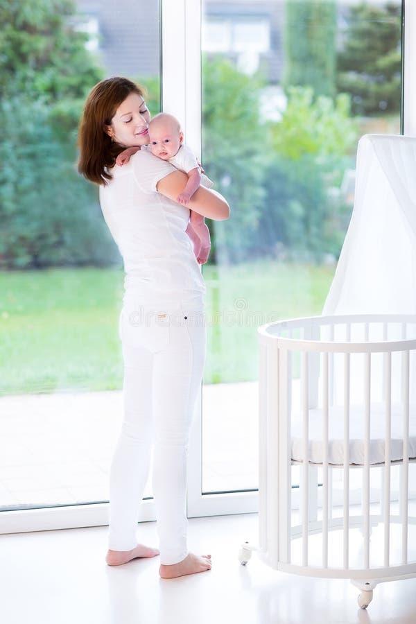 Sira de mãe a pôr o bebê recém-nascido na cama ao lado da janela fotografia de stock