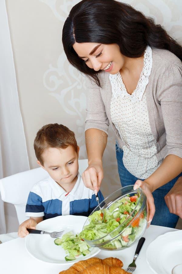 Sira de mãe a pôr a salada sobre a placa de seu filho fotografia de stock royalty free
