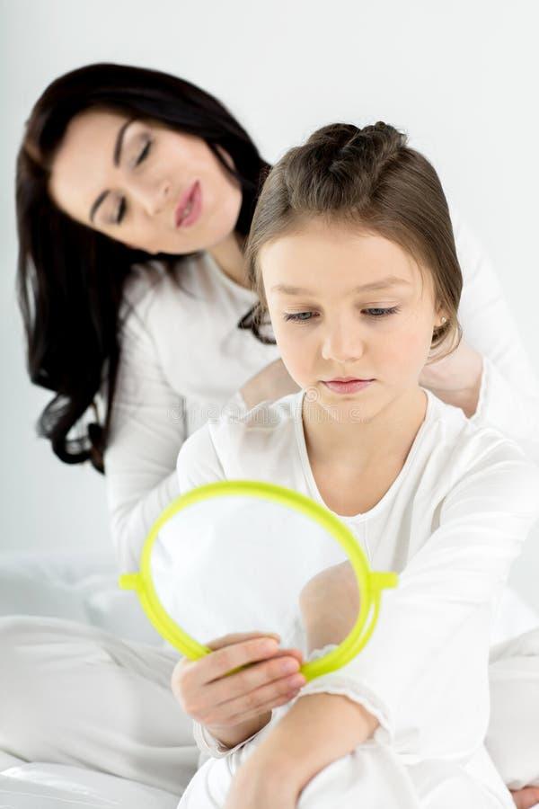 Sira de mãe a pentear o cabelo da filha pequena bonito com espelho de mão imagens de stock