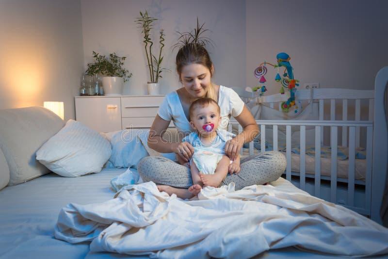 Sira de mãe a tecidos em mudança a seu filho do bebê na cama na noite fotografia de stock royalty free