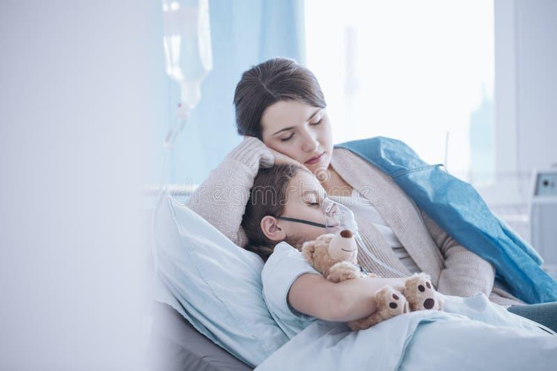 Sira de mãe a tomar da filha doente com máscara de oxigênio e peluche b fotos de stock