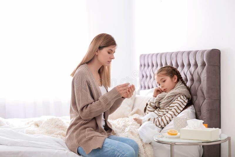 Sira de mãe a tomar da filha pequena que sofre do frio foto de stock royalty free