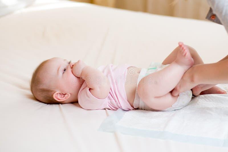 Sira de mãe a tomar do bebê pequeno e a mudar o tecido foto de stock royalty free