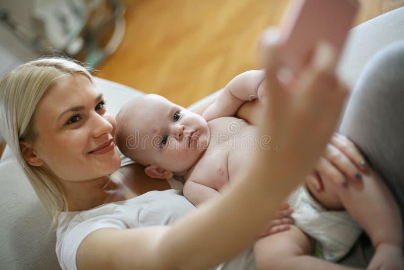 Sira de mãe a tomar o autorretrato de seu e seu bebê em casa fotografia de stock royalty free