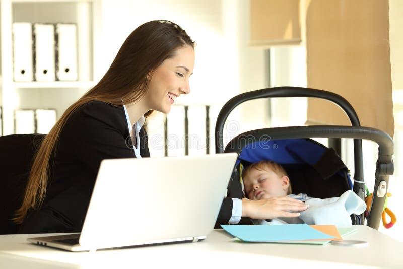 Sira de mãe a trabalhar e a tomar de seu filho do bebê fotos de stock royalty free
