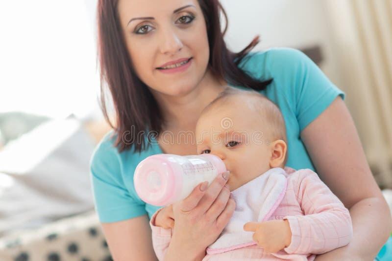 Sira de m?e ao beb? de alimenta??o com garrafa imagens de stock royalty free