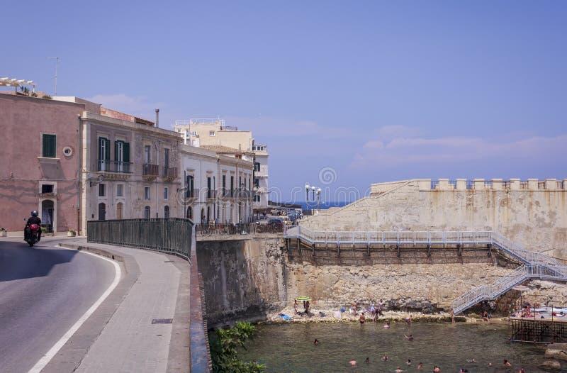 Siracusa, Σικελία, Ιταλία †«στις 12 Αυγούστου 2018: οι άνθρωποι λούζουν στη θάλασσα κοντά στη δύσκολη ακτή του νησιού Ortygia O στοκ εικόνες