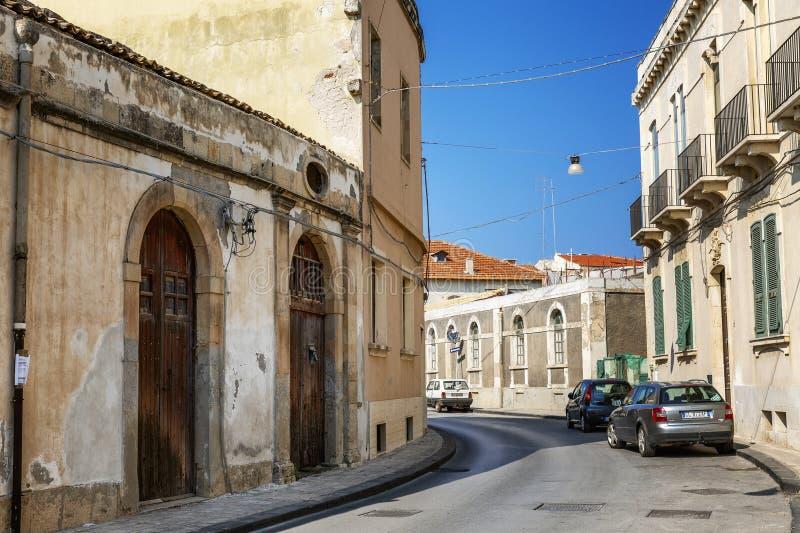 Siracusa, W?ochy, 08/25/2016: Ulica w Sicily z starymi domami w w?oszczyzna stylu przeciw niebieskiemu niebu fotografia stock