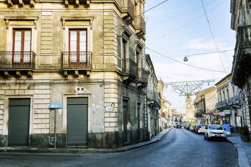 Siracusa, W?ochy, 08/27/2016: Ulica w Sicily z starymi domami w w?oszczyzna stylu przeciw niebieskiemu niebu zdjęcie stock