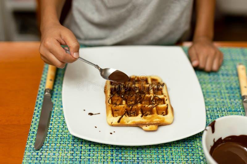 Sirap för choklad för barnhand hällande på dillanden i den vita plattan på frukosttid arkivbilder
