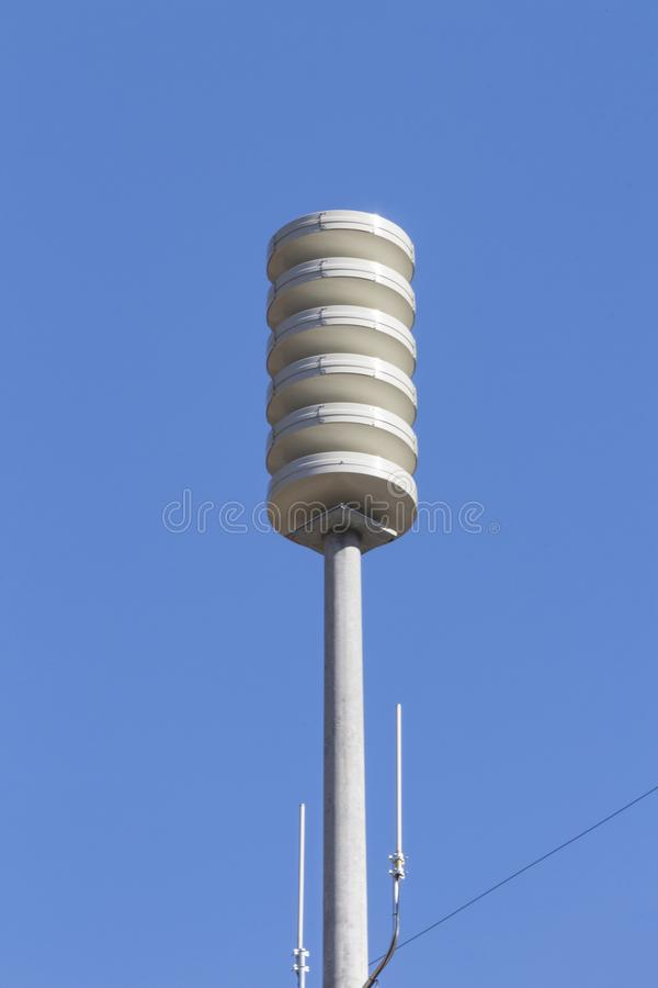 Siren tower alone against a blue sky. Vertical aspect, centered, space for text stock image