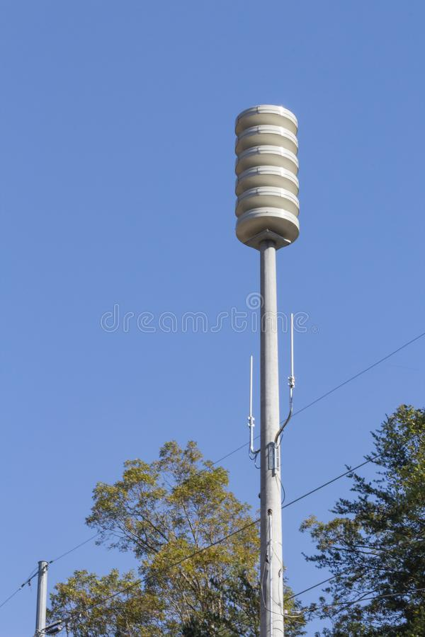 Siren tower over tree tops against a clear blue sky, space for text,. Vertical aspect stock photography