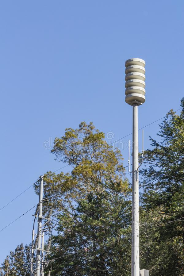 Siren tower rising between trees, against a blue sky, space for text. Vertical aspect stock image
