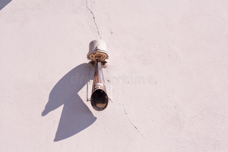 Sirena aherrumbrada vieja en una pared de la casa foto de archivo libre de regalías