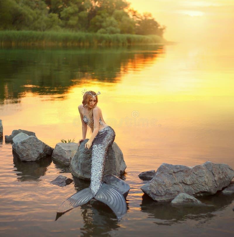 Sirena en la piedra el sentarse en la puesta del sol en las rocas fotografía de archivo
