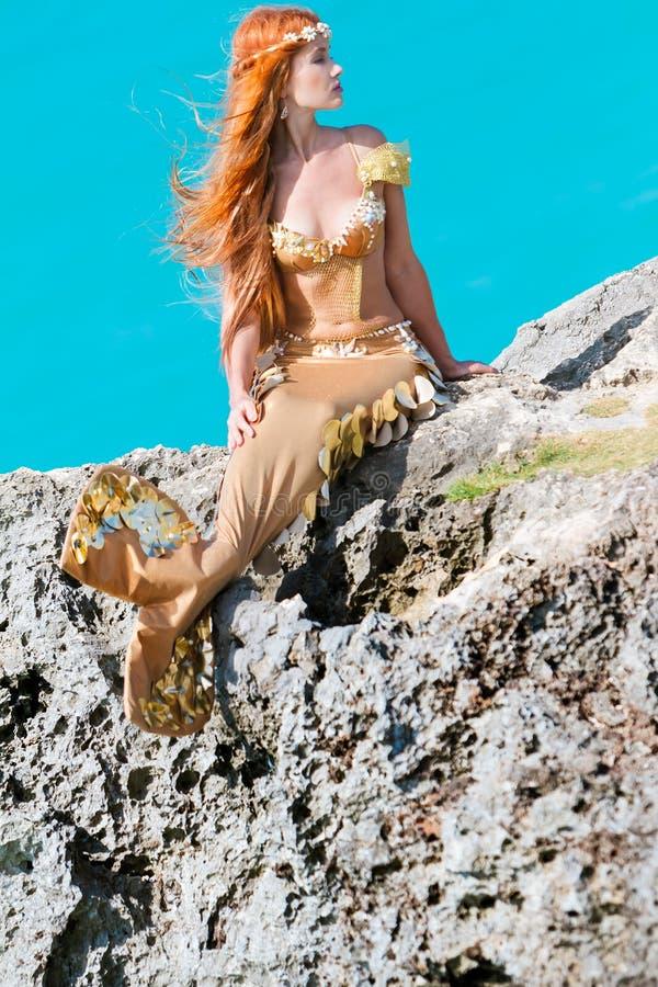Sirena en la roca fotos de archivo