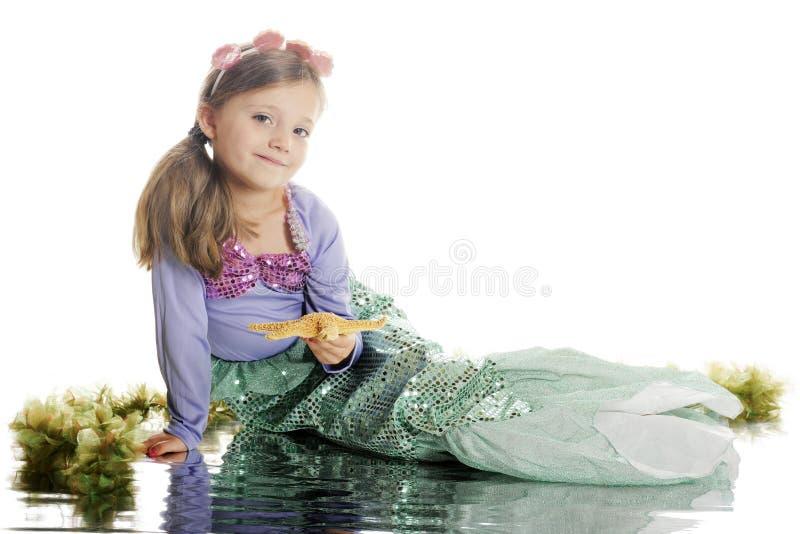 Sirena, feliz con una estrella de mar fotografía de archivo
