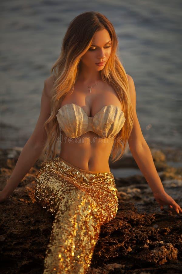Sirena hermosa que se sienta en una roca imágenes de archivo libres de regalías