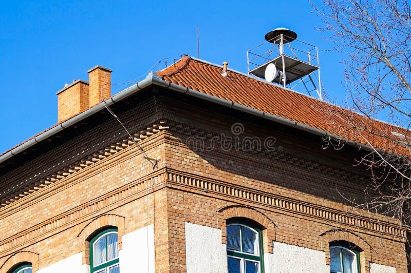 Sirene op de bovenkant van een baksteengebouw stock foto's