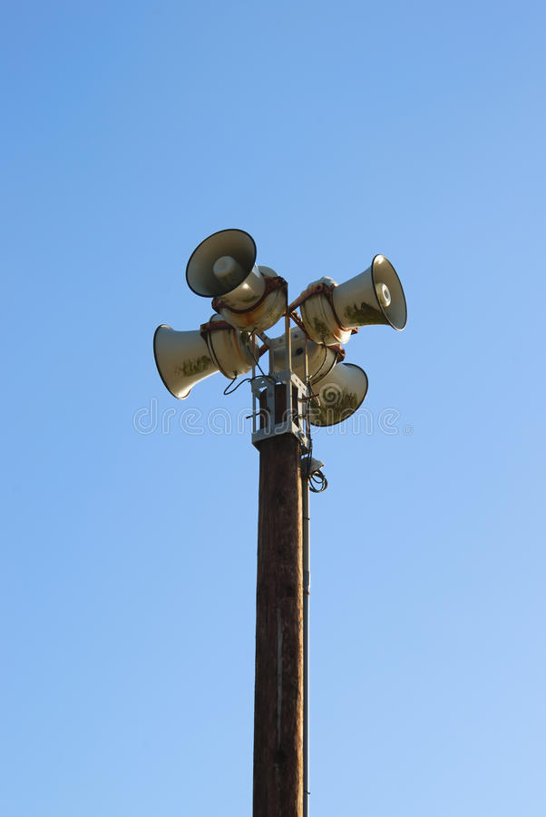 Sirens. Four sirens on a pole with blue sky in the background royalty free stock photo