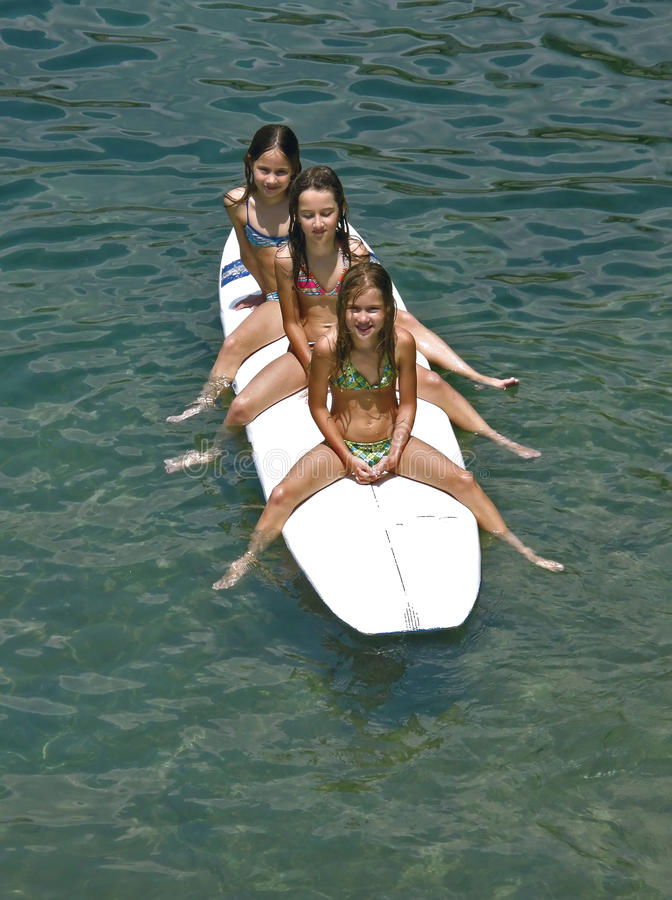 Sirens - surfing children. Sea sirens, sisters (best friends) spending summer holidays sitting on surf desk on Adriatic sea (Croatia-Dalmatia royalty free stock photos