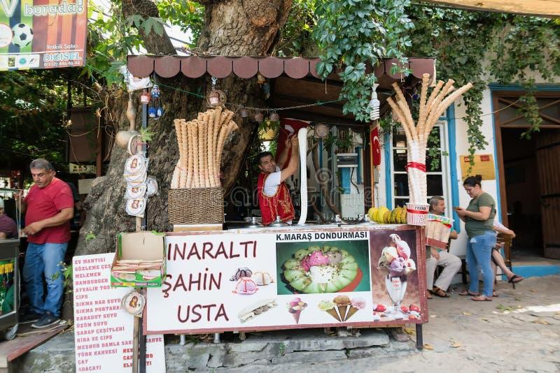 SIRINCE, TURQUÍA - 17 DE AGOSTO DE 2017: Un hombre en traje turco tradicional vende el helado en la calle foto de archivo