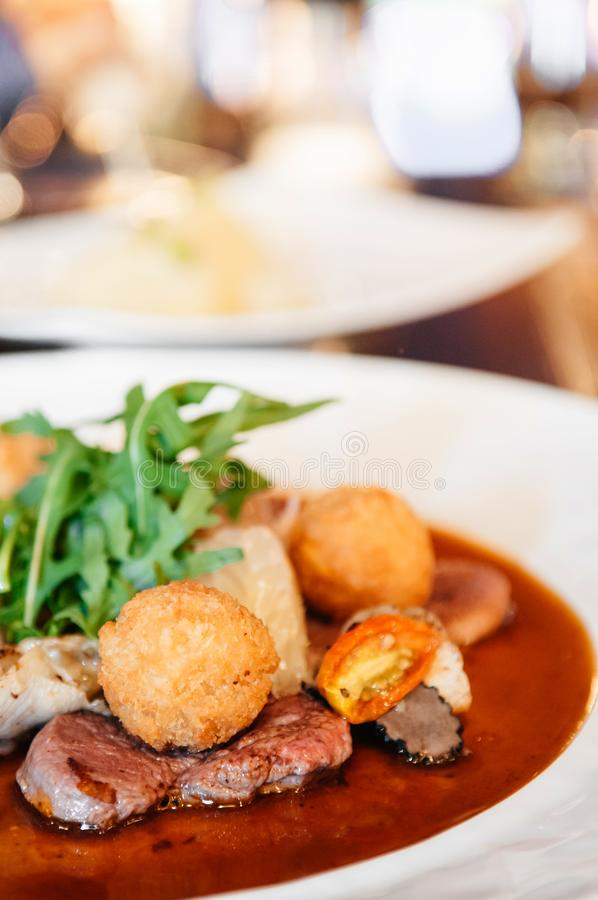Sirloin beef steak with potato crogettes and arugula salad and g stock photos